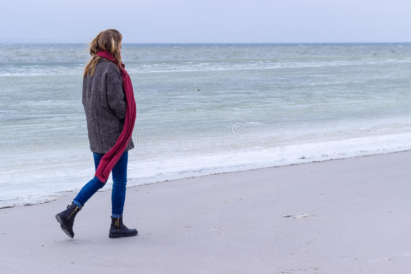 Lone sad beautiful girl walking along the shore of the frozen sea on a cold day, rubella, chicken with a red scarf on the neck. Lone sad beautiful girl walking stock photography