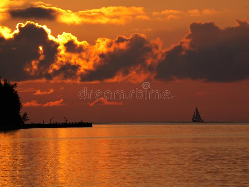 Sailing away to the  Sunset. A lone sail boat is silhouetted against the setting sun in Door County Wisconsin stock photo