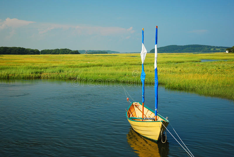 Lone Sail. A lone sailboat is tied to a dock on the Essex River stock photos