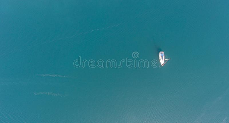 A lone sailing yacht at anchor. Aerial view. royalty free stock photo