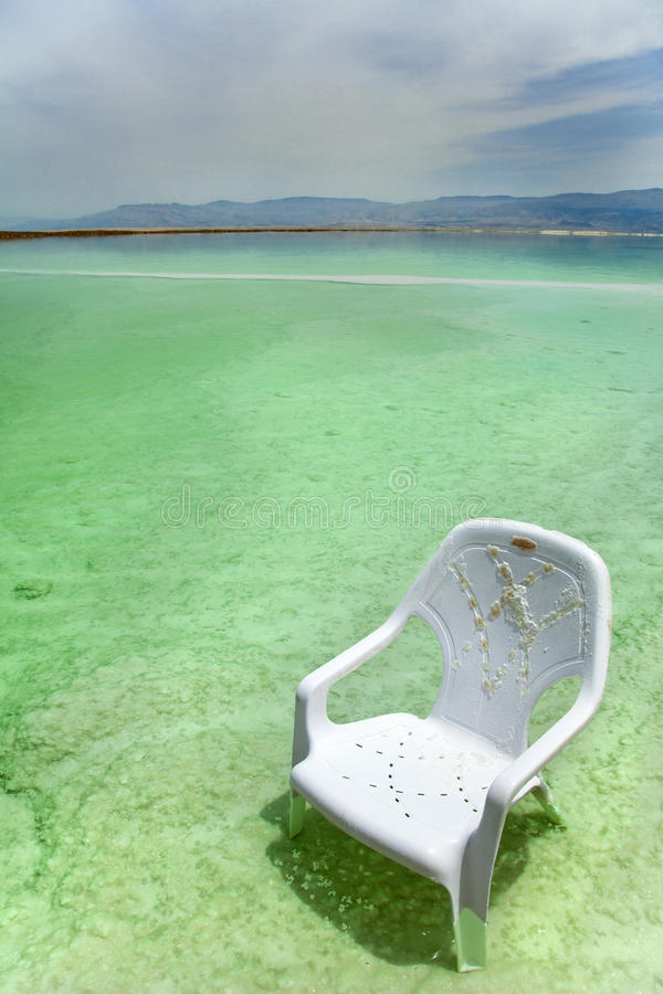 Easy Chair at the Dead Sea. A lone salt covered plastic easy chair in the shallow waters of the world famous Dead Sea, Israel stock image