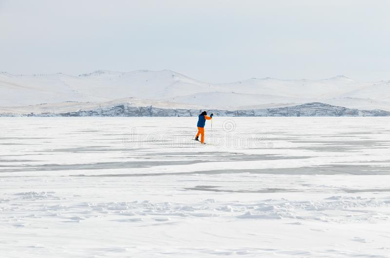 Man skiing through snow and ice surface Lake Baikal. Lone skier in middle of Baikal Small Sea skiing through snow and ice surdace royalty free stock photography