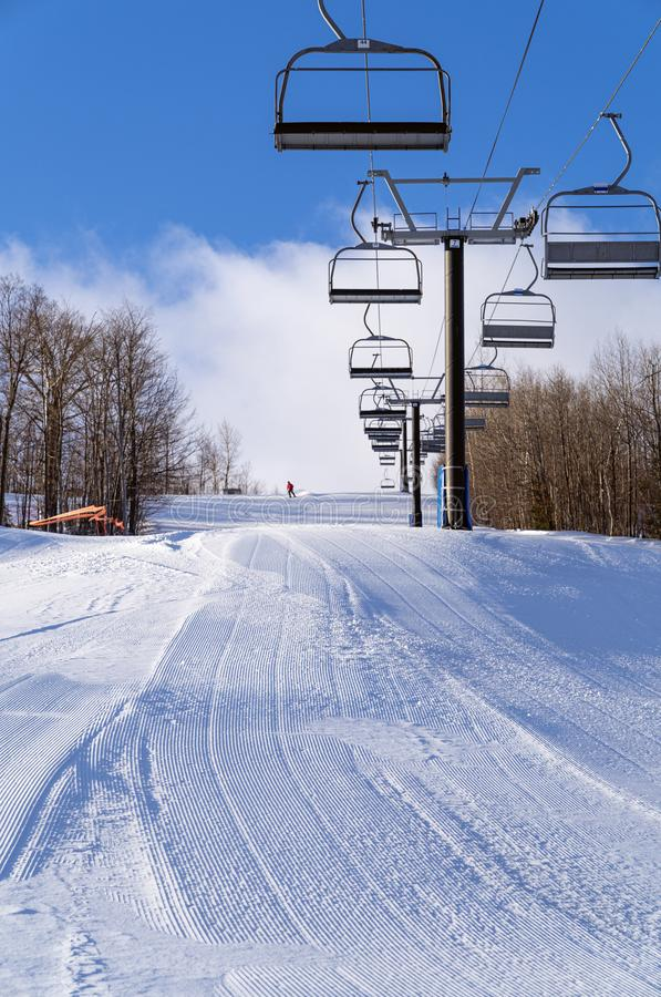 A lone skier descends a groomed run with a chairlift at a ski hill. A lone skier takes the first run down a groomed trail with a chairlift at a ski hill stock image