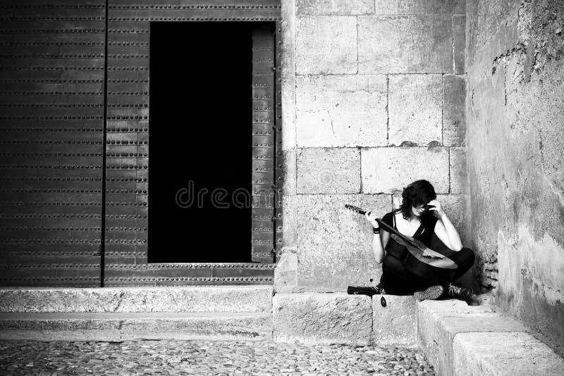 Lone street artist. Near old iron door stock photos