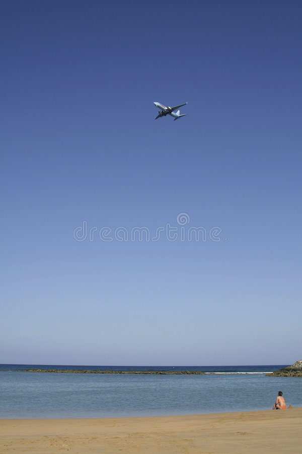 Download Lone Sunbather Watches Her Plane Leave Stock Image - Image: 1449799