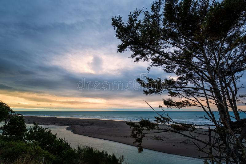 Lone Tree and a Winter Sunset in Northern California. A lone tree looks over the Pacific Ocean at sunset on a winter evening stock images