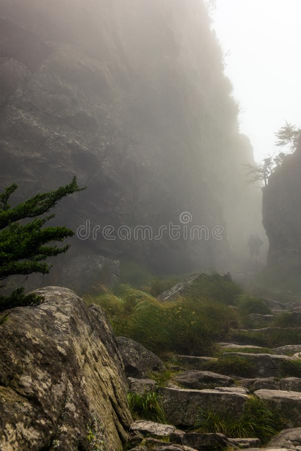 A lone trekker passing a rock gorge with steep walls royalty free stock image