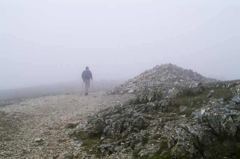 Lone walker in mist by mountain cairn stock photo