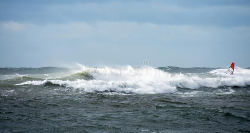 Lone wind surfer riding the waves stock photography