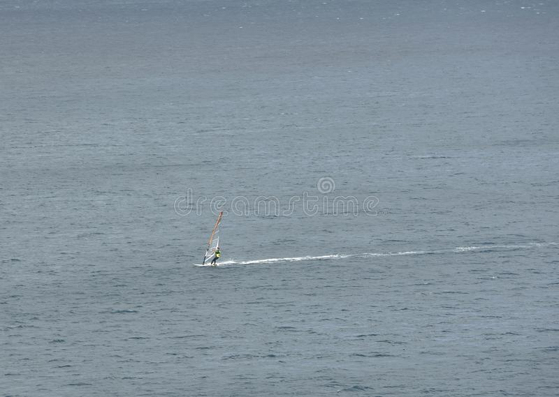 Lone windsurfer crossing the harbour stock photography