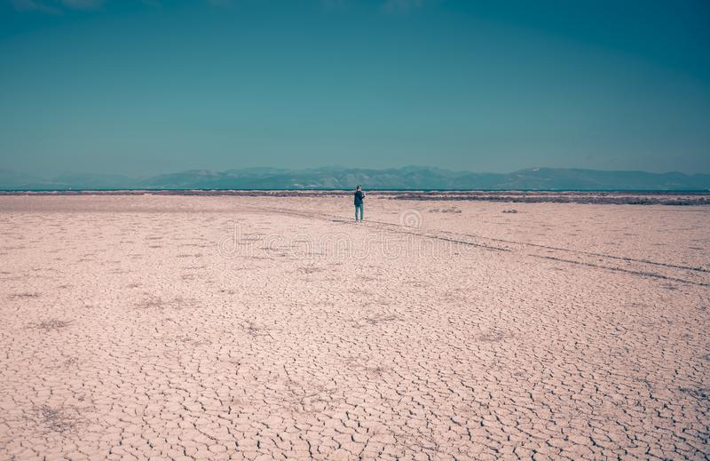 A lone woman is wondering around a dry salt lake. Amazing Greece stock images