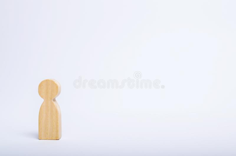 A lone wooden human figure stands on a white background. A person is waiting, standing and waiting. Style of minimalism, space stock images