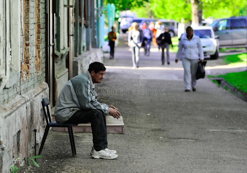 Depression. Lonely man. The lonely man sits on the street. Nearby there pass people stock images