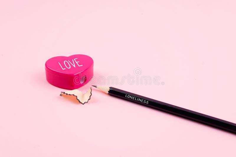 Loneliness, Love, relationship, romance concept. Pink heart pencil sharpener and pencil with shavings on pink background. Lonely minimal pastel rose heart stock images