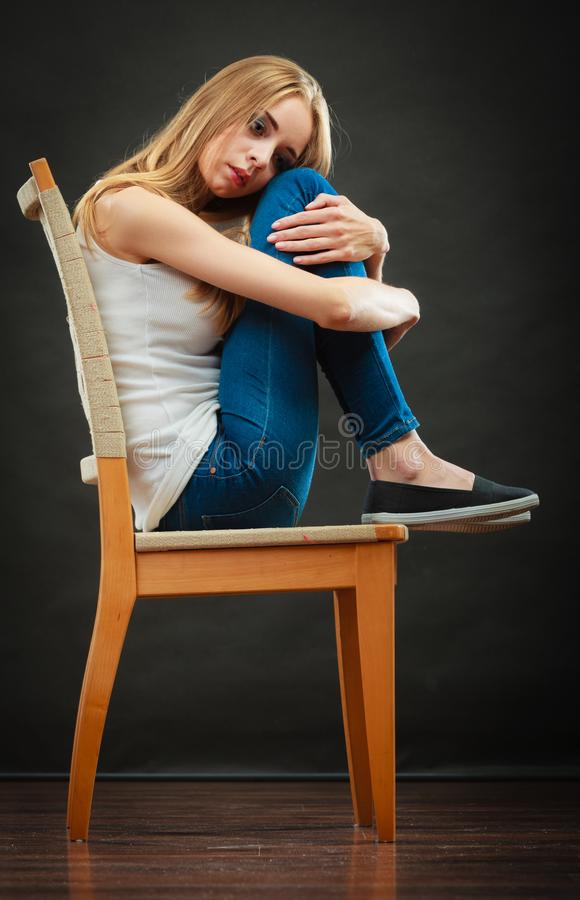 Oung sad woman sitting on chair stock photo