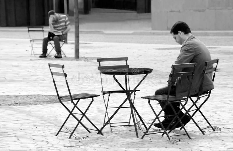 Loneliness. Non staged view of two lonely men sitting alone in the street walk on a sunday morning, indifferent to each other, in Porto, Portugal