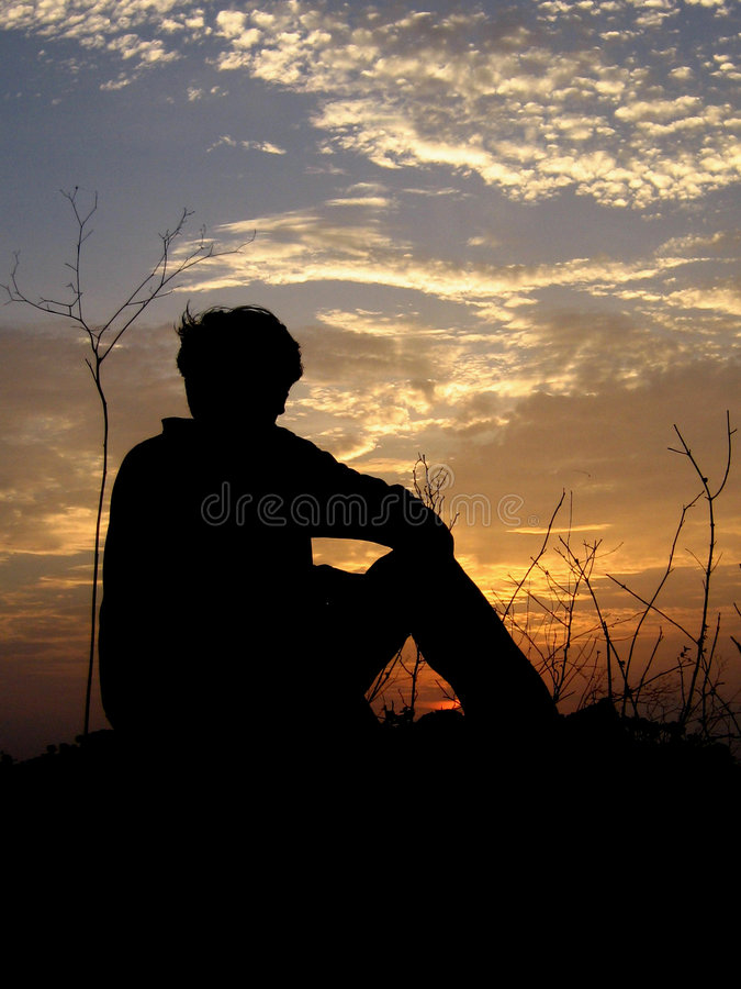 Lonely. A lonely boy watches a sunset royalty free stock photos