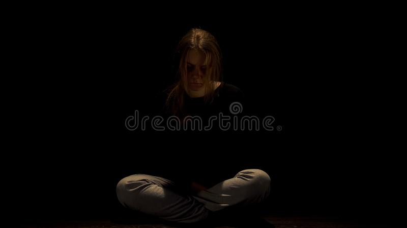 Lonely abused female sitting in darkness, miserable victim of domestic violence. Stock photo stock photos