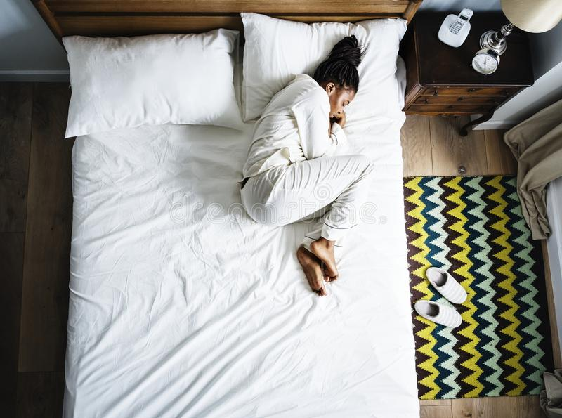 Lonely African American woman on bed sleeping alone stock photos