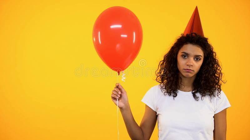Lonely african woman holding red balloon, feeling sad on birthday celebration stock photos