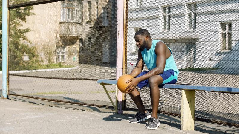 Lonely Afro-American sportsman sitting on bench and holding ball, depression stock image
