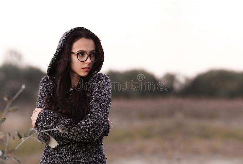 Lonely alone beautiful girl in warm sweater with hood looking aside in autumn field background. Picture of pretty depressed sad un stock images