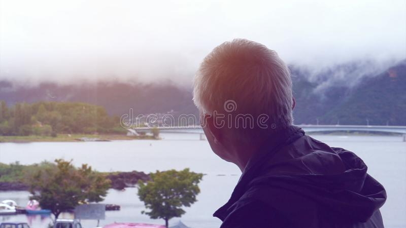 Lonely Asian senior man looking at view alone miss his wife. Lonely Asian senior man looking at view alone royalty free stock image