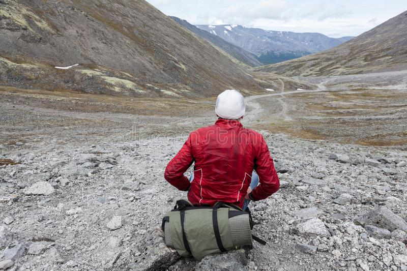Lonely backpacker sitting on stone and looking at distance, the only one way through the valley stock image