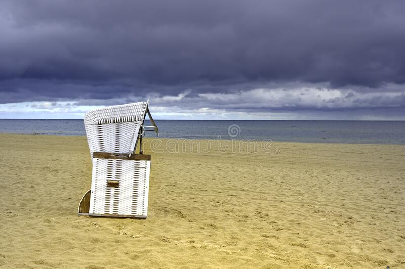 Lonely beach with a beach chair on Usedom. Overlooking the sea to dramatic looking storm clouds royalty free stock photography