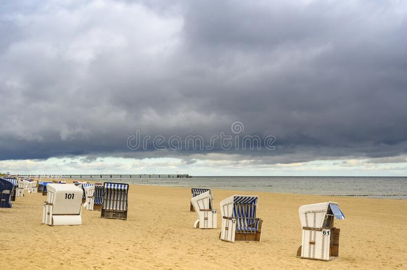Lonely beach with a beach chair on Usedom. Lonely beach with beach chairs on Usedom overlooking the sea to dramatic looking storm clouds stock photo