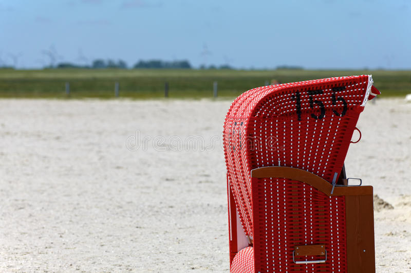 Lonely beach chair. Red Wicker beach chairs on the beach of the Baltic Sea royalty free stock photography
