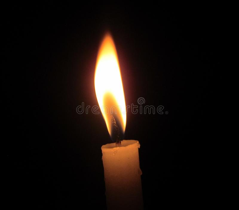A LONELY BEAM OF CANDLE LIGHT, BURNING ITSELF THROUGH THE NIGHT. royalty free stock photos