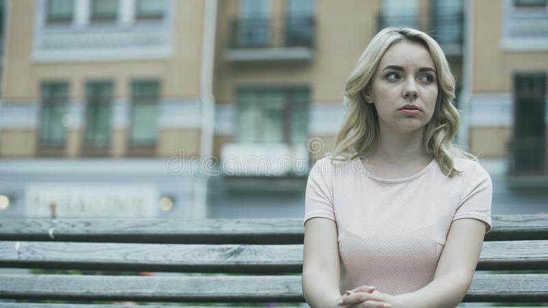 Lonely beautiful young lady sitting alone, suffering problems, feeling sad stock images