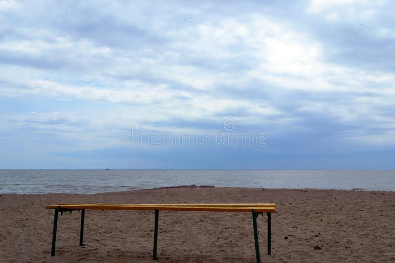 A lonely bench on the beach. Sky stock photography