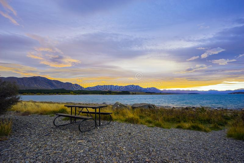 Lonely bench with beautiful sunset landscape at background. royalty free stock photos