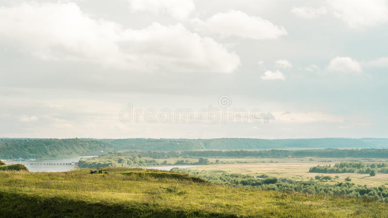 A lonely bench on a hill with a distant view stock image