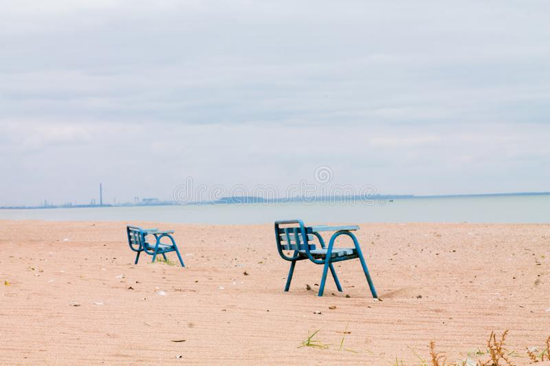 Lonely benches in an abandoned village in the area of hostilities in Ukraine. View from the Sea of Azov to Mariupol. Smoking. Chimneys by the sea. Ecological stock images