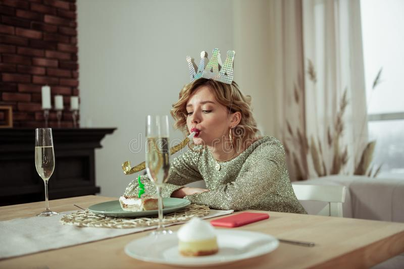 Lonely birthday woman sitting and looking at the piece of cake. Piece of cake. Lonely birthday woman wearing shiny dress sitting and looking at the piece of cake stock image