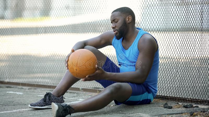 Lonely black basketball player sitting on stadium ground and holding ball, sport stock photo