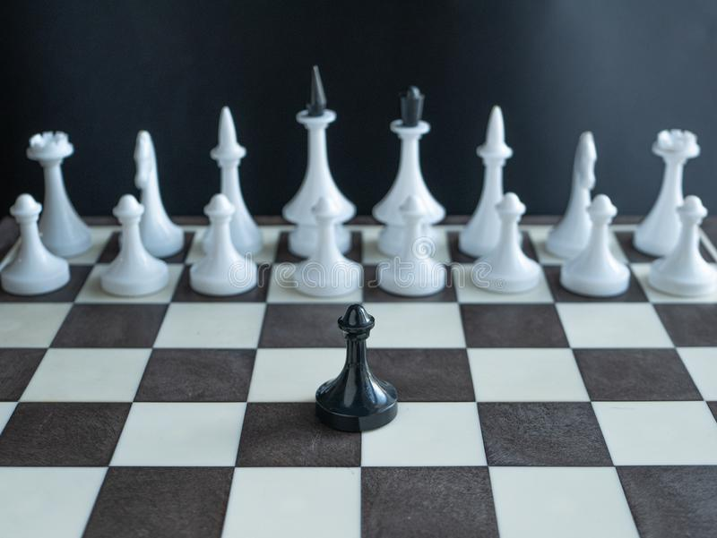 Lonely black pawn standing alone against whole army of white figures on chess board. concept depict one man army famous Martin royalty free stock photography