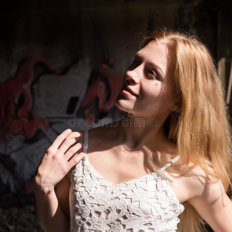 Lonely blondy woman in a whit translucent blouse in abandoned building stock image
