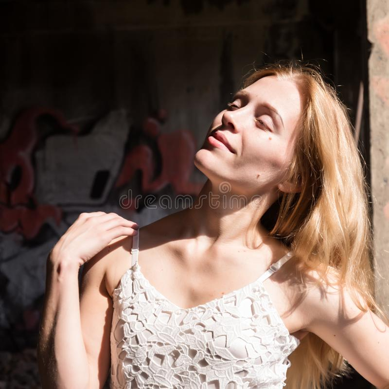 Lonely blondy woman in a whit translucent blouse in abandoned building royalty free stock photos