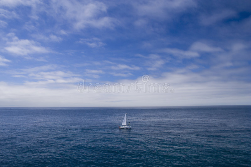 The lonely boat. A lonely boat sailing in the ocean stock photo