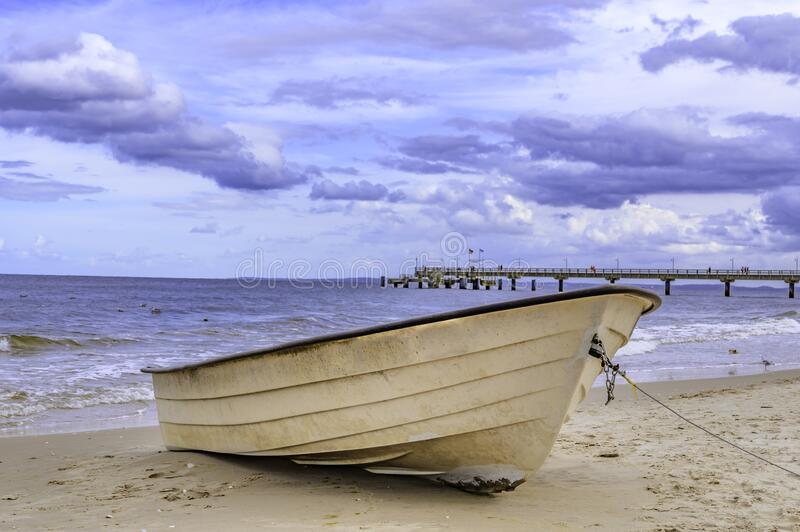 Lonely boat lying on the sand beach at the coast of the island usedom, Germany. Under a blue and cloudy sky stock photos