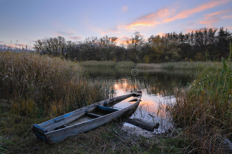 Lonely boat. Lonely old boat at dawn in the autumn stock photography