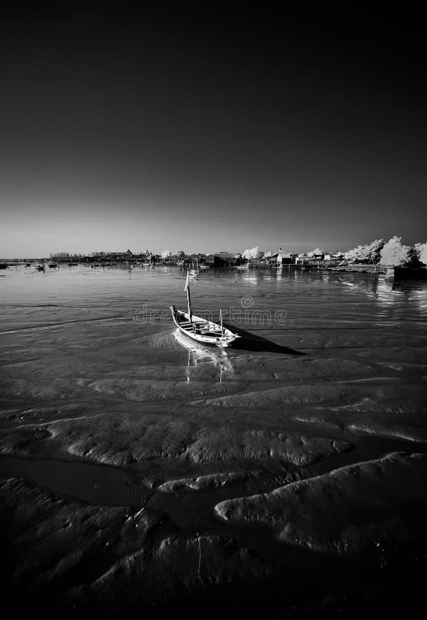 Lonely boat on receding shore. Taken at Kenjeran beach, Surabaya, east Java, Indonesia royalty free stock photo
