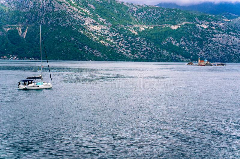Lonely boat sailing to the lighthouse of the The Virgin of the Cliff in the Bay of Kotor royalty free stock image