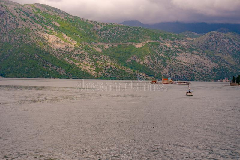 Lonely boat sailing to the lighthouse of the The Virgin of the Cliff in the Bay of Kotor royalty free stock images