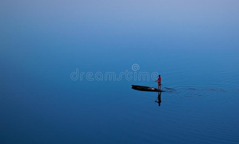 The lonely boatman. The boatman was standing all alone on a river and was trying to reach the bank of the river as soon as possible royalty free stock image