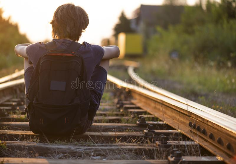 A lonely boy sitts on the railroad tracks royalty free stock images